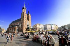 Touristen auf dem Hauptmarkt von Krakau - im Hintergrund Bürgerhäuser und die römisch katholische Marienkirche; sie wurde vom 13. bis zum Beginn des 15. Jahrhundert errichtet.