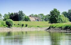 Lauf der Pinnau - Reetdachhaus hinter dem Deich - Bäume und Büsche am Ufer.