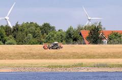 Das Gras des  Elbdeichs wird mit einem Trecker gemäht - im Hintergrund die Rotoren von Windrädern in den Hamburger Vierlanden.