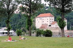 Wiese auf  der Landspitze an der die Inn in die Donau mündet - Menschen liegen auf Decken in der Sonne - am gegenüberliegenden Donauufer die Veste Niederhaus an der die Ilz in die Donau fliesst.