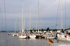 Sportboothafen Brunsbüttel neben der Schleuse - Segelboote und Motorboote liegen nebeneinander am Steg. Im Hintergrund lks. die Hochbrücke Brunsbüttel der Bundesstrasse 5.