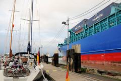 Ein mit Containern beladenes Frachtschiff fährt aus der Schleusenkammer Schleuse Brunsbüttel in den Nord-Ostsee-Kanal ein - lks. Sportboote im Yachthafen an der Schleuse.