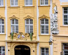 Eingang Barock Hotel in Bamberg - Kreuzigungsgruppe aus Stein an einer Hausfassade.