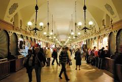 Innenansicht Tuchhallen von Krakau - kleine Verkaufsstände, Souvenirs in den Arkaden - Touristen kaufen Andenken.