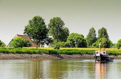 Bauernhaus zwischen Bäumen hinter dem Deich an der Stör - das Arbeitsschiff Steindeich fährt störaufwärts.