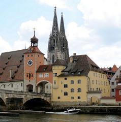 Steinerne Brücke über die Donau in Regensburg mit Brückturm, der ein Teil der ehemaligen Stadtbefestigung Regensburg ist. Im Hintergrund die zwei gotischen Kirchtürme des Doms St. Peter. Ein Sportboot fährt auf der Donau stromaufwärts.