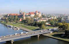 0223Blick auf den Wawel -  Burganlage - Residenzschloss - Kathedrale St. Stanislaus und Wenzel in Krakau / Kraków. Uferpromenade - Grünanlage an der Weichsel - Wisla; Brücke über den Fluss.