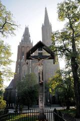 Christus am Holzkreuz - im Hintergrund die Kirche St. Michaelis in Wroclaw, Brelau - Polen.