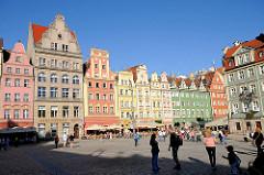 Historische Häuser am Marktplatz / Großer Ring von Wroclaw, Breslau / Polen - Cafés und Restaurants mit Markisen vor den Häusern. Touristen gehen über den grossen Platz.