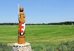 Holzskulptur am Ufer der Oste an der Fährverbindung Brobergen - der Broberger Roland - Symbol der Freiheit und Gerechtigkeit - weite Felder und Wälder im Hintergrund.