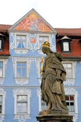 Skulptur Kaiserin Kunigunde auf der Oberen Brücke in Bamberg, dahinter die bemalte Fassade eines Wohn- und Geschäftsgebäudes.