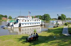 Die Oste bei Oberndorf - Männer sitzen im Schatten auf einer Bank und blicken auf den Fluss; auf dem Wasser das Restaurantschiff Ostekieker.