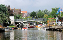 Gracht mit Fussgängerbrücke - Sportboote am Ufer des Kanals.
