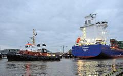 Der Containerfeeder EMOTION  fährt am frühen Morgen mit Hilfe eines Schleppers in die Schleusenkammer der Brunsbüttler Schleuse des Nord-Ostsee-Kanals ein.