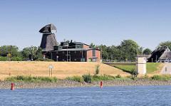 Elbdeich mit ehem. Mühle in Hamburg Altengamme - am Elbufer rote Fahrwassertonnen  am rechten Flussufer; gelbes Kreuz markiert den Übergang der Fahrtrinne zur anderen Seite der Elbe.