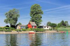 Wochenendhäuser am Ufer der Elbe - Sportboote am Flussufer.