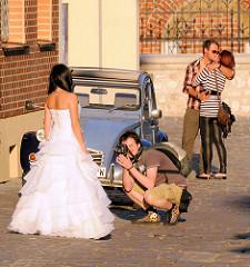 Fotoshooting mit Brautkleid / Braut; der Fotograf kniet in kurzen Hosen auf dem Pflaster - küssendes Paar; Strassenszene aus Krakau.