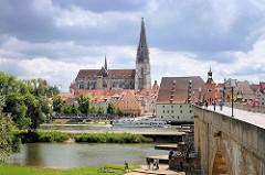 Blick über die Donau zum Regensburger Dom St. Peter / Kathedrale St. Peter - rechts die Steinerne Brücke und der Brückturm mit dem Salzstadl - ein Ausflugsschiff fährt auf der Donau. Am Brückenpfeiler sitzen Jugendliche in der Sonne am Donauufer.