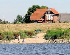 Wohnhaus hinter dem Deich - Sandstrand an der Elbe - Angler in der Morgensonne am Wasser