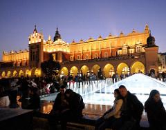 Nachtaufnahme Marktplatz von Krakau - beleuchteter Springbrunnen; im Hintergrund die angestrahlten Tuchhallen - Renaissancearchitektur, erbaut Ende des 16. Jahrhunderts.