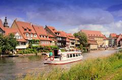 Fahrgastschiff mit Touristen auf der Regnitz - am Ufer Wohnhäuser Bambergs.