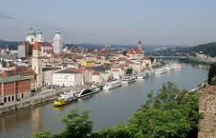 Blick vom St. Georgsberg auf die Altstadt von Passau an der Donau. Flusschiffe liegen am Ufer des Flusses.