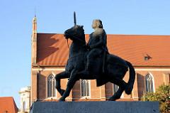 Statue König Boleslaw auf einem Pferd - im Hintergrund das Kirchenschiff der St. Dorothenkirche in Wroclaw, Breslau - Polen.