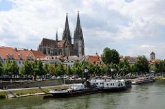 Blick über die Donau auf den Dom St. Peter - Fahrgastschiffe / Ausflugsboote liegen am Ufer des Flusse.