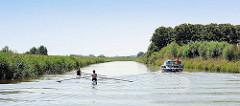 Zwei Ruderer / Einer auf der Krückau - ein Sportboot passiert die beiden Wassersportler.