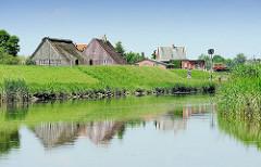 Lauf der Pinnau - Häuser hinter dem Pinnaudeich spiegeln sich im Wasser.