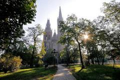 Park, Grünanlage der St. Michaelis Kirche Wroclaw, Breslau - Polen; die tiefstehende Sonne scheint durch die Bäume.