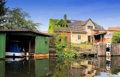Pegelanzeige der lichten Durchfahrtshöhe einer Brücke in Grabow - Bootshaus am Kanal, Wohnhaus mit Efeu bewachsen.