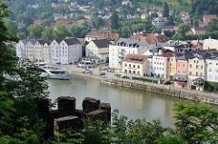 Blick vom St. Georgsberg auf die Altstadt von Passau an der Donau. Uferpromenade mit Wohnhäusern an der Donau - im Vordergrund Zinnen der Befestigungsanlage der Veste Oberhaus.