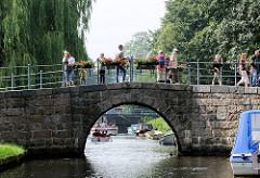 Gracht mit schmaler Brücke in Friedrichstadt - Touristen fotografieren die Stadt.