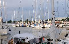 Sportboothafen Brunsbüttel neben der Schleuse - Segelboote und Motorboote liegen nebeneinander am Steg.