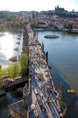 Blick auf die historische Karlsbrücke - die Brücke über die Moldau wurde im 14. Jahrundert errichtet. Sie ist einer der ältesten Steinbrücken Europas. Die alte Brücke ist eine der vielen Sehenswürdigkeiten Prags - dicht gedrängt überqueren dort die T