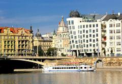 Moderne und historische Architketu am Ufer der Moldau in Prag - Fahrgastschiff mit Touristen auf der Moldau.