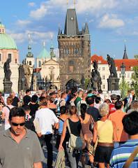 Sehrenswürdigkeit in Prag - Touristen auf der Karlsbrücke - im Hintergrund Brückentürm und Kirchtürme - Steinskulpturen von Heiligen über den Brückenpfeilern.