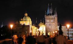 Sehenswürdigkeit in Prag - Touristen auf der Karlsbrücke bei Nacht, am Abend - im Hintergrund Brückentürm und Kirchtürme - Steinskulpturen von Heiligen über den Brückenpfeilern.