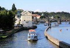 Ein Fahrgastschiff auf seiner Tour auf der Moldau in Prag - im Hintergrund die historische Karlsbrücke, die im 14. Jahrundert errichtet wurde. Sie ist mit einer der ältesten Steinbrücken Europas.