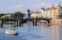 Wohnhäuser - Etagenhäuser mit farbig gestalteter Hausfassade am Ufer der Moldau in Prag - ein Touristenschiff auf seiner Tour über die Moldau.