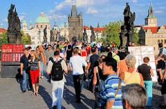 Sehenswürdigkeit in Prag - Touristen auf der Karlsbrücke - im Hintergrund Brückentürm und Kirchtürme - Steinskulpturen von Heiligen über den Brückenpfeilern.
