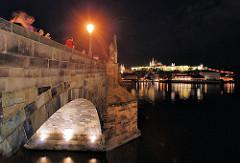 Blick auf die historische Karlsbrücke bei Nacht; sie wurde im 14. Jahrundert errichtet. Sie ist einer der ältesten Steinbrücken Europas. Brücke ist eine der vielen Sehenswürdigkeiten Prags - dicht gedrängt überqueren dort die Touristen zu Fuß die Mol