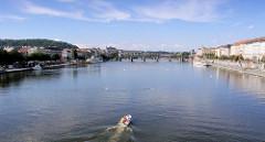 Ein Sportboot fährt auf der Moldau durch Prag - im Hintergrund die historische Karlsbrücke; siewurde im 14. Jahrundert errichtet. Sie ist einer der ältesten Steinbrücken Europas.
