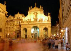 Prag bei Nacht - Touristen bevölkern die Strasse - die historischne Gebäude der Prager Altstadt sind hell angestrahlt.