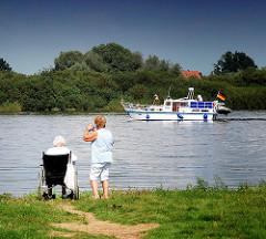 Motorboot auf der Elbe bei Hitzacker - zwei Frauen, eine im Rollstuhl, blicken vom Flussufer  auf das vorbeifahrende Sportboot.