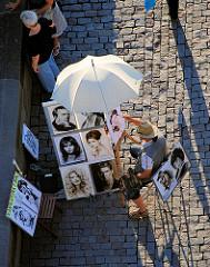 Ein Künstler malt auf dem Pflaster der historischen Prager Karlsbrücke Portraits unter einem Sonnenschirm.