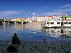 Ein Angler sitzt mit seinen Angeln an der Moldau in Prag - Wohnhäuser im Hintergrund; ein Fahrgastschiff auf seiner Rundfahrt.