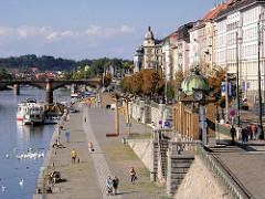 Uferpromenade an der Moldau in der tschechischen Hauptstadt Prag - Anleger für Touristenschiffe, mehrstöckige Wohnhäuser - unterschiedliche Architekturstile.
