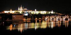 Nachtaufnahme in Prag - Blick über die Moldau zur beleuchteten Prager Burg und dem Veitsdom - rechts die historische Karlsbrücke über den Fluss.